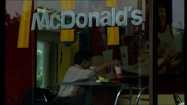 barack obama's former school man seated in mcdonald's restaurant/ indonesian flag on flagpole - mcdonald's stock-videos und b-roll-filmmaterial