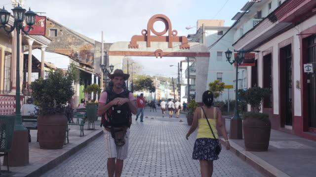 Baracoa Cuba colonial city main square with yello townhall. Establishing shot / b-roll
