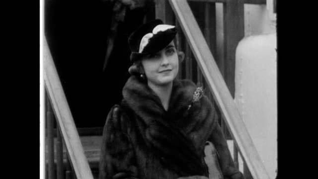 vídeos y material grabado en eventos de stock de / barbara hutton stands at the bottom of steps, smiling at the camera / answers questions for the press on the return from her year long honeymoon.... - 1934