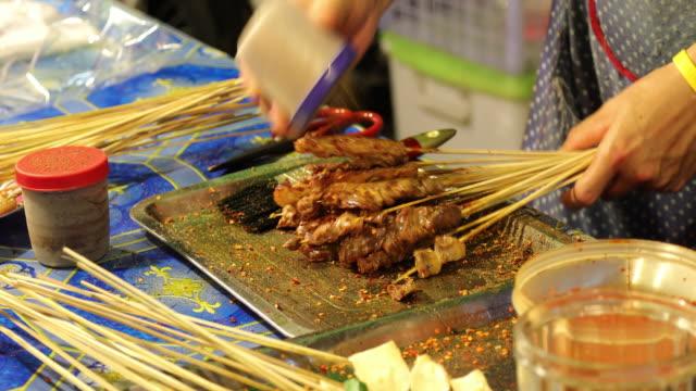 barbecue am nachtmarkt in thailand - fleischzange stock-videos und b-roll-filmmaterial