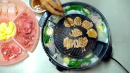 Barbecue Grill on Korean Pan. Closeup Pork Slice grilled in Korean Restaurant.