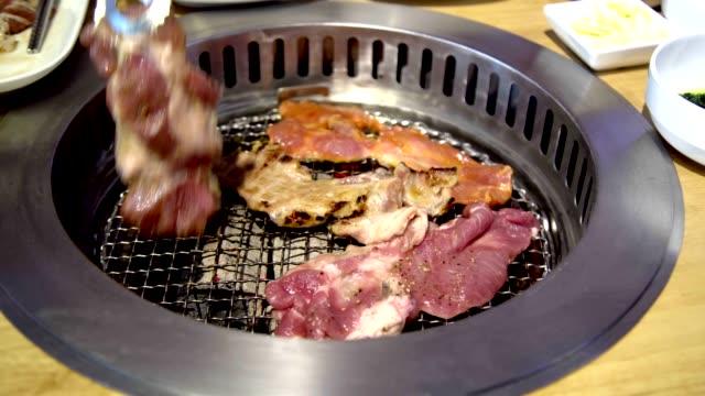 grill grill auf koreanischem pan. closeup pork slice gegrillt in korean restaurant. - tablett oder küchenblech stock-videos und b-roll-filmmaterial