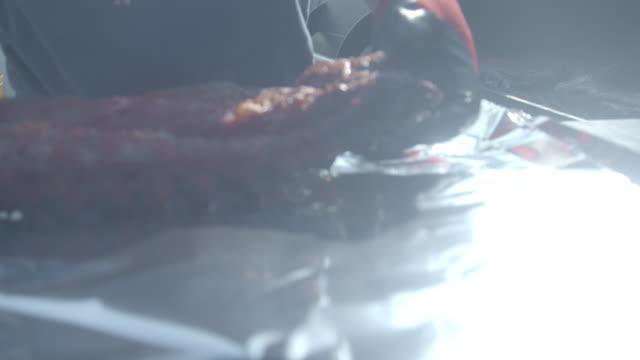 stockvideo's en b-roll-footage met barbecue pitmaster trekt een rek van sappige gerookte varkensvlees baby rug ribben van een commerciële roker en wraps in aluminiumfolie te worden geserveerd - het zuiden van de verenigde staten