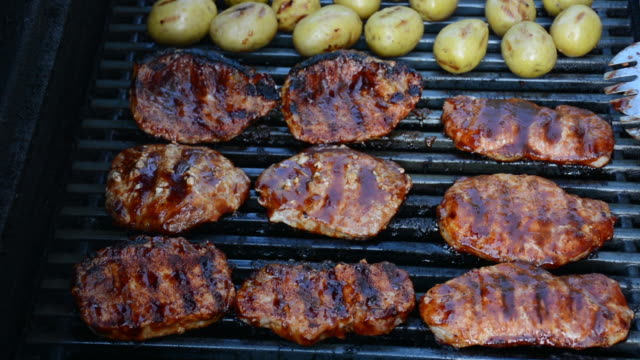 cu barbecue pork chops being flipped on a grill - kotelett stock-videos und b-roll-filmmaterial