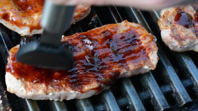 vídeos de stock, filmes e b-roll de cu barbecue sauce being spread over pork chops on a grill - bbq sauce