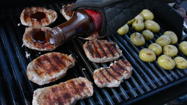 barbecue sauce poured over pork chops on a grill with potatoes - oven mitt stock videos and b-roll footage