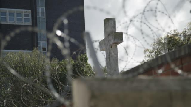 barbed wire and cross, rack focus - 宗教上のシンボル点の映像素材/bロール