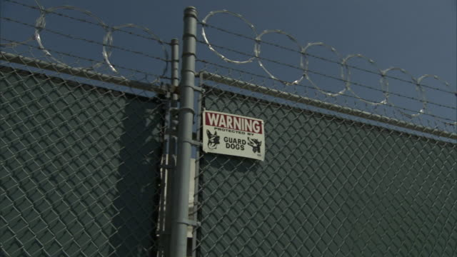 barbed wire coils around a chain link fence and bears a sign that warns of guard dogs. - barbed wire stock videos & royalty-free footage