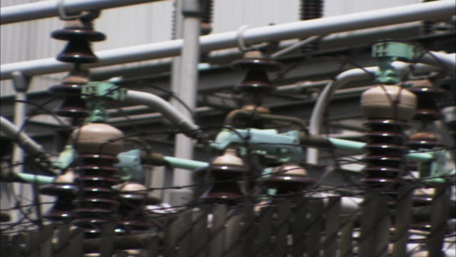 Barbed wire coils surround high voltage insulators at a power plant.