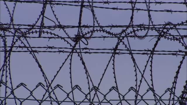 cu, pan, barbed wire fence against sky, singapore - barbed wire stock videos & royalty-free footage