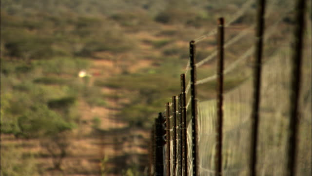 a barbed wire fence encloses a game reserve. - wildlife reserve stock videos & royalty-free footage