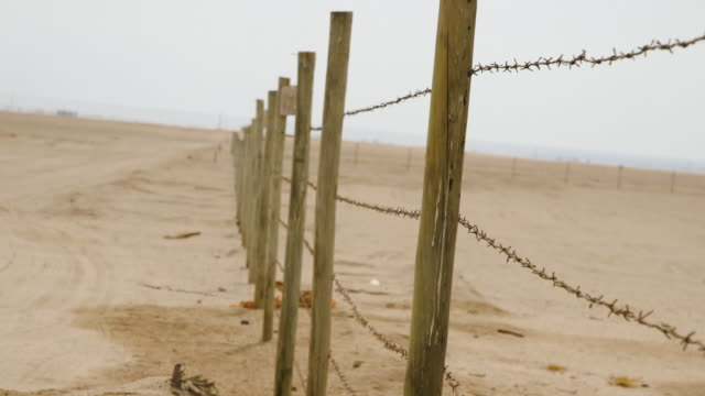 barbed wire fence in chilean desert, close-up - barbed wire stock videos & royalty-free footage