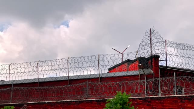 barbed wire fence  of the city prison - fence stock videos & royalty-free footage