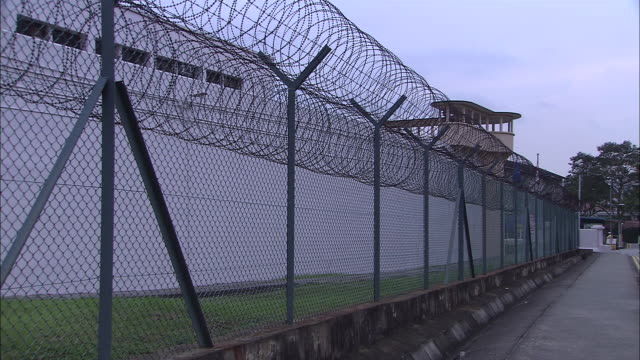 vidéos et rushes de ms, barbed wire fence surrounding prison, guard tower in background, singapore - clôture
