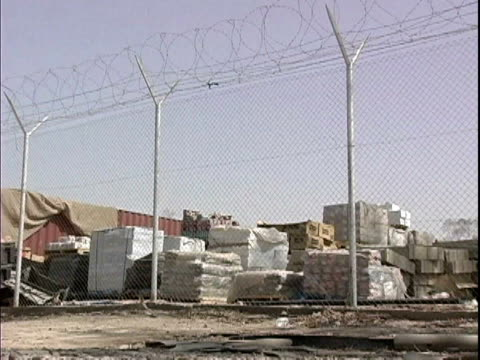 barbed wire fence surrounding supplies at camp victory / baghdad iraq / audio - campo militare video stock e b–roll