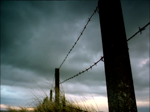 barbed wire fence under large grey clouds england - stacheldraht stock-videos und b-roll-filmmaterial