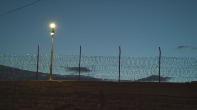 """vidéos et rushes de clôture de fil de fer barbelé au crépuscule entourant le pénitencier des états-unis, installation maximale administrative supermax prison complex à florence, colorado (comté de fremont)-l' """"alcatraz des rocheuses"""" - social justice concept"""
