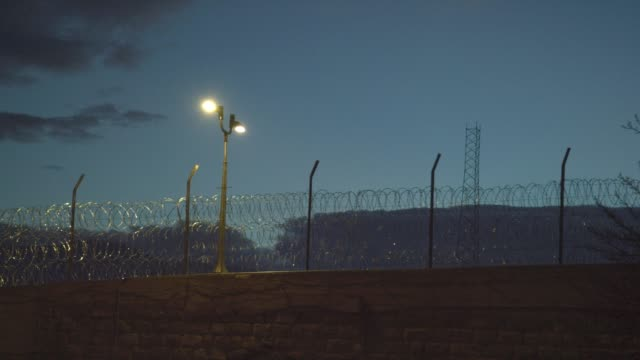 "barbed wire fencing at dusk surrounding the united states penitentiary, administrative maximum facility supermax prison complex in florence, colorado (fremont county) - the ""alcatraz of the rockies"" - recinzione video stock e b–roll"