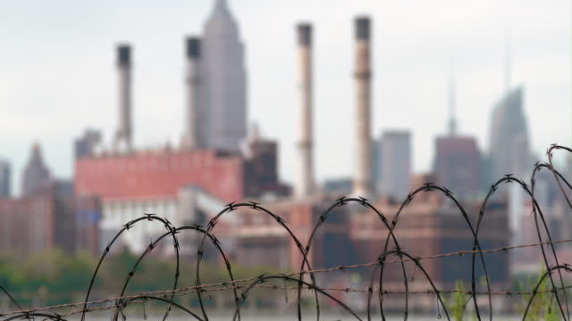 cu of barbed wire obscuring an out of focus powerstation and empire states building. - keep out sign stock videos & royalty-free footage