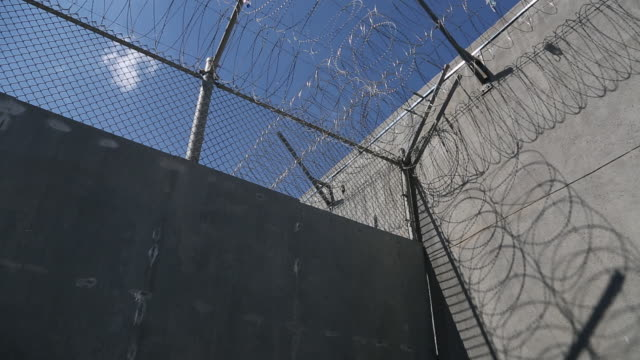 barbed wire on prison wall - prison stock videos & royalty-free footage