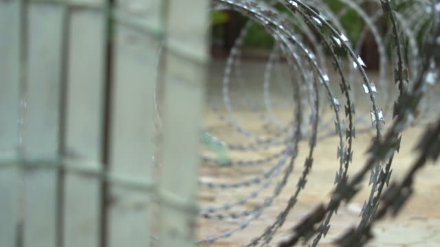 barbed wire on the fence. prison fence - boundary stock videos & royalty-free footage
