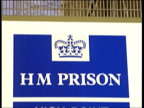 barbed wire on top of prison fence refocus wire fence in f/g tilt down to sign 'hm prison high point' ms road signs at side of road for 'kedington'... - bury st edmunds stock videos & royalty-free footage