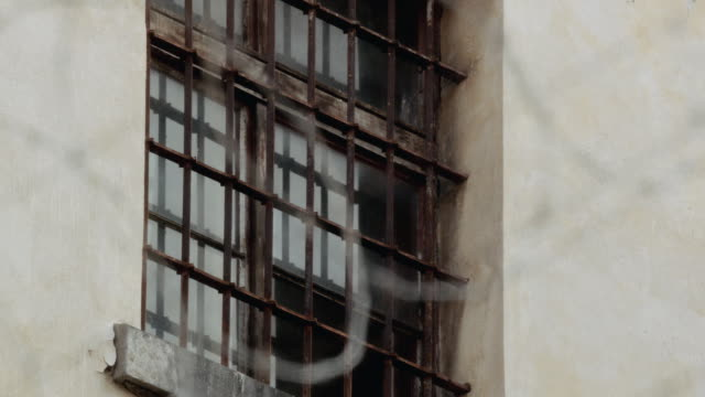 r/f barbed wire surrounding a stone building with iron bars over its windows - iron bars for windows stock videos & royalty-free footage