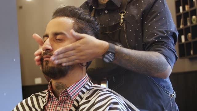 barber applying aftershave to customer in salon - etnia latino americana video stock e b–roll