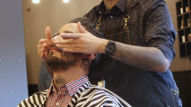 barber applying aftershave to customer in salon - head stock videos & royalty-free footage