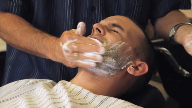 CU Barber applying shaving cream on client's face / Madison, Florida, USA