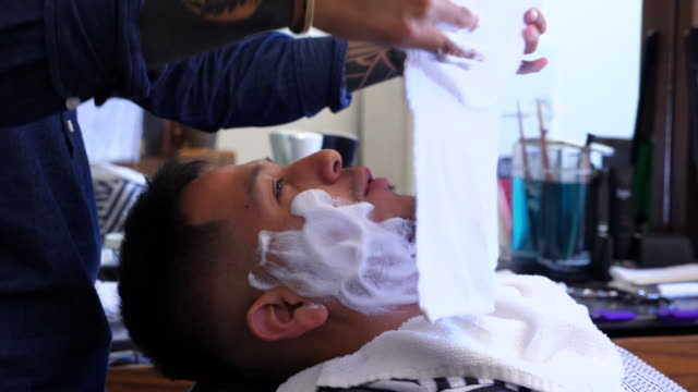 ms td barber applying towel to mans face before shave in barber shop - shaving stock videos and b-roll footage