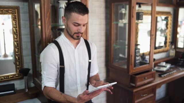barber überprüft die heutige terminplanung - suspenders stock-videos und b-roll-filmmaterial