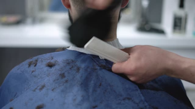 barber cleaning customer's neck and ears after haircut - sweeping stock videos & royalty-free footage