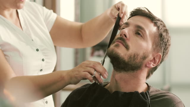 Barber cut a client's beard with clippers