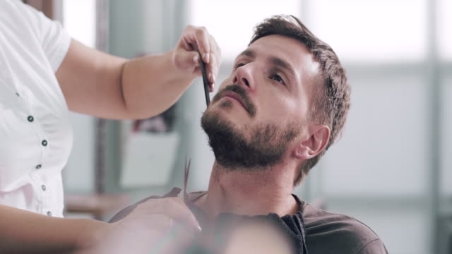 vídeos de stock, filmes e b-roll de cortar a barba de um cliente com tesoura de barbeiro - tesoura