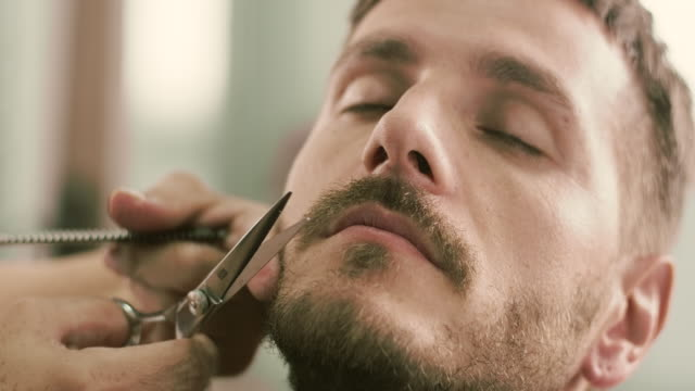 barber cut a client's mustache with clippers - barba peluria del viso video stock e b–roll