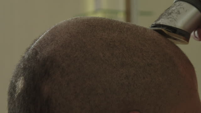 vídeos de stock, filmes e b-roll de barber cuts hair of client with clipper - raspando