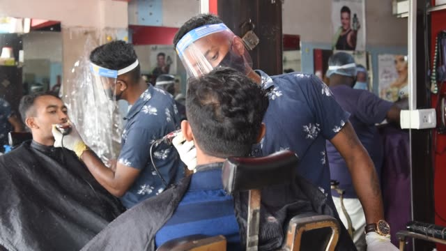 barber cuts hair wearing protective shield after ease covid19 lockdown guwahati sunday june 7 2020 - short hair stock videos & royalty-free footage