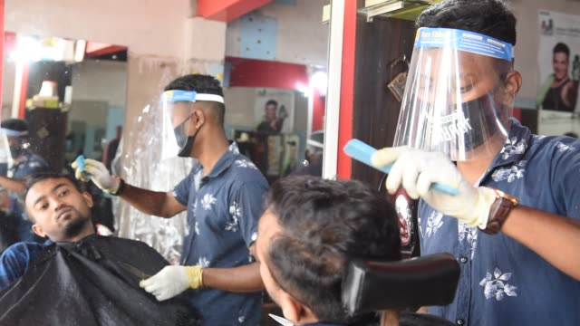barber cuts hair wearing protective shield, after ease covid-19 lockdown, guwahati, sunday, june 7, 2020. - short hair stock videos & royalty-free footage