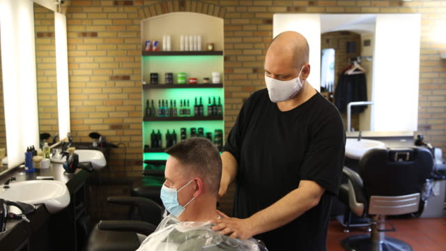a barber cuts the hair of a customer as both of them wear protective face masks at a barber shop open for the first day since march during the novel... - human face stock videos & royalty-free footage