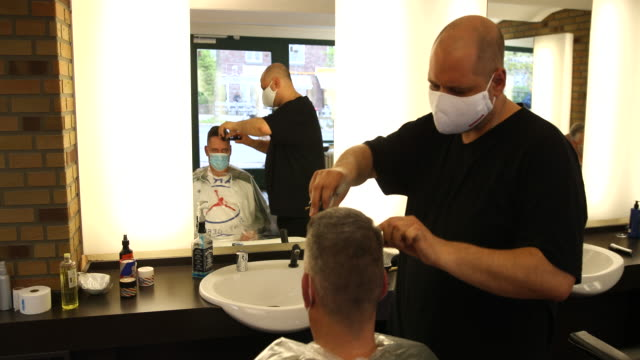 barber cuts the hair of a customer as both of them wear protective face masks at a barber shop open for the first day since march during the novel... - opening stock videos & royalty-free footage