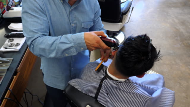 ms ha barber cutting clients hair with trimmers - hair clipper stock videos & royalty-free footage