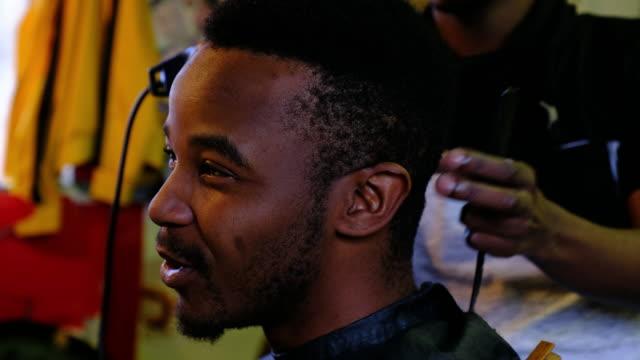 vídeos y material grabado en eventos de stock de sus clientes del corte de pelo con una recortadora de pelo del peluquero - etnia negra