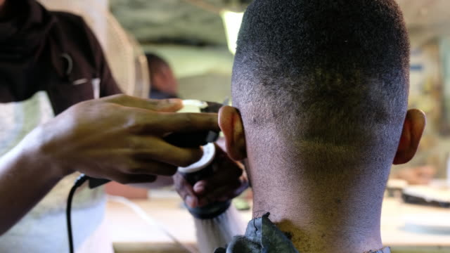 Barber cutting his clients hair with a hair clipper