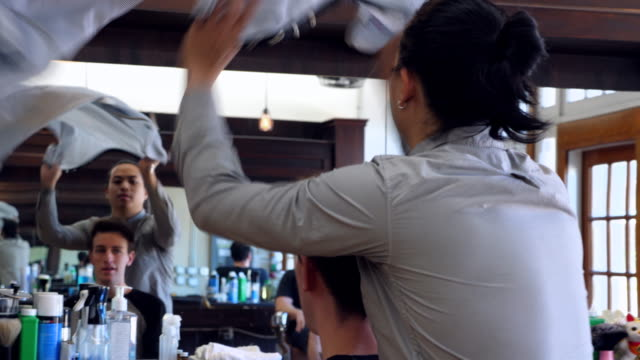 ms r/f barber draping cape over client before hair cut in barber shop - beauty salon stock videos and b-roll footage