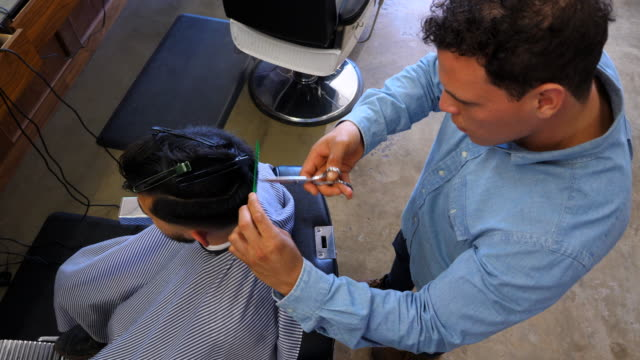 vídeos de stock, filmes e b-roll de ms ha barber focused on trimming clients hair with scissors during hair cut - controlo de qualidade