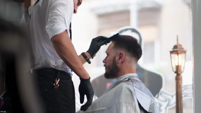 barber giving a haircut in his barber shop - barber stock videos & royalty-free footage