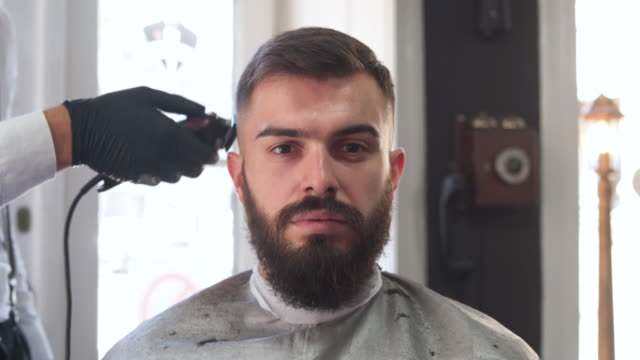 barber giving a haircut in his barber shop - barber chair stock videos & royalty-free footage