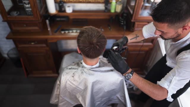 barbier gibt seinem kunden einen haarschnitt mit haarschneider - suspenders stock-videos und b-roll-filmmaterial