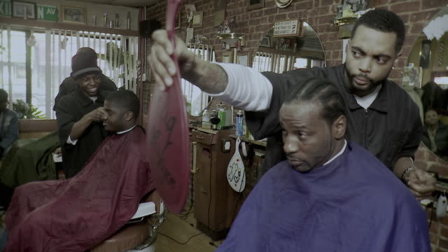 MS Barber holding mirror for customer, other men having haircuts in background, Brooklyn, New York City, New York State, USA